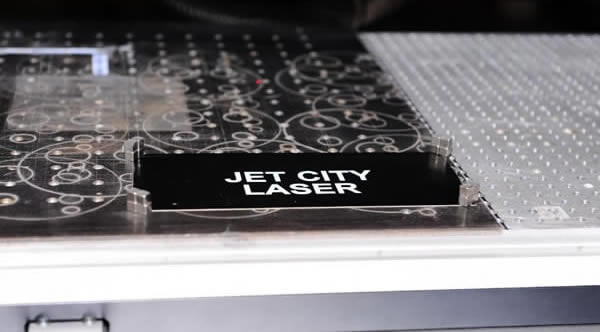 Laser etched black anodized aluminum exhibits bright white characters